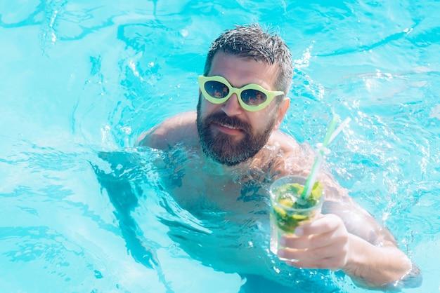 モヒートを持つ男。プールでひげを生やした男とのカクテルパーティー。
