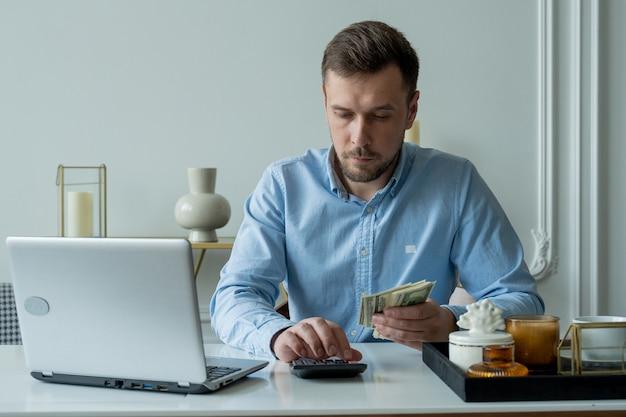 Человек с деньгами и калькулятором проверяет счета, подсчитывает расходы, изучает кредитный баланс, сидя за столом дома