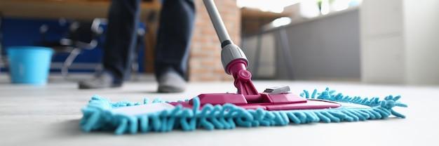 モップを持った男がオフィスの床を洗う。清掃会社のサービスコンセプト