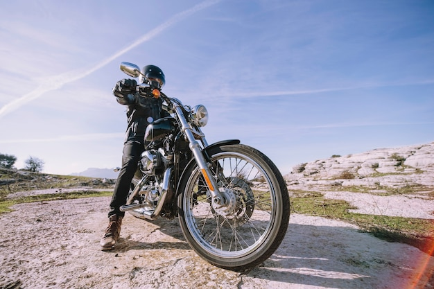 Man with motorbike on rock
