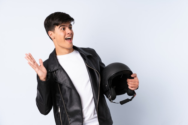 Man with a motorcycle helmet over blue wall with surprise facial expression