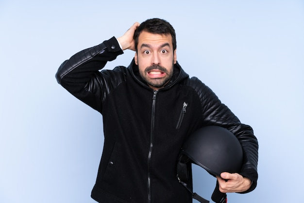 Man with a motorcycle helmet over isolated wall frustrated and takes hands on head