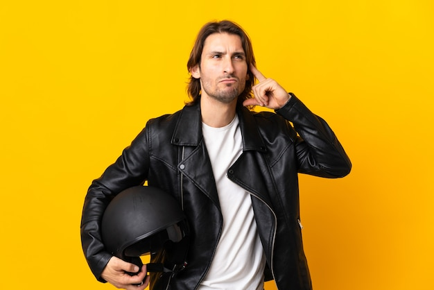 Man with a motorcycle helmet isolated on yellow having doubts and thinking