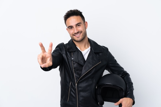 Man with a motorcycle helmet smiling and showing victory sign
