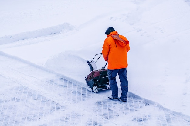 電動トラックドライブ除雪機を持った男は、雪道の細部にある除雪機である雪を取り除きます。湿った大雪を取り除くためのモーターマシン。除雪機。