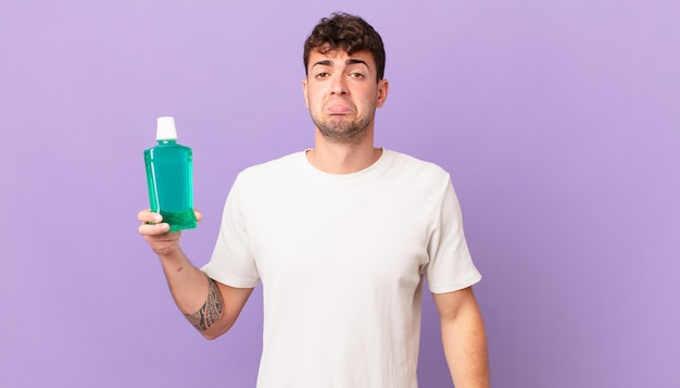 Man with mouthwash feeling sad and whiney with an unhappy look, crying with a negative and frustrated attitude