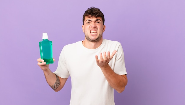 Man with mouthwash looking desperate and frustrated, stressed, unhappy and annoyed, shouting and screaming