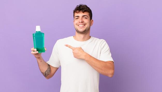 구강청결제를 하고 있는 남자는 기분 좋게 웃고, 옆과 위쪽을 가리키며 복사 공간에 물건을 보여줍니다.