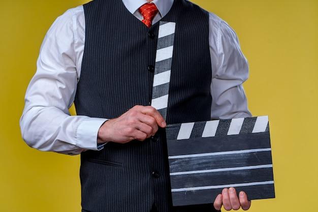 Человек с заслонкой фильма во время съемок. обрезанное фото. производство фильма. человеческие эмоции.