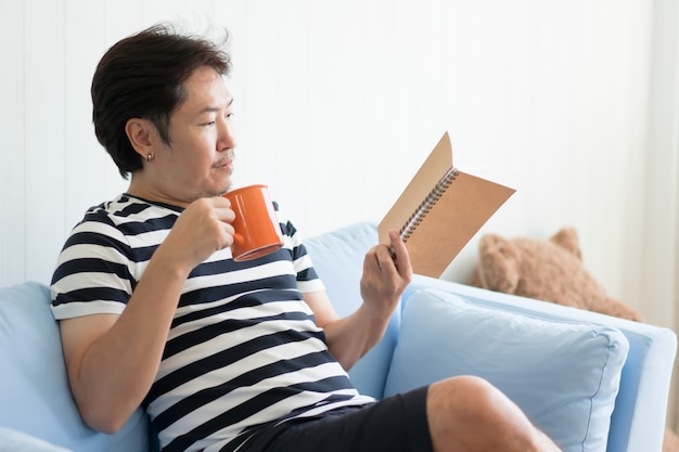 Man with a mug and reading a book for relax in living room at home