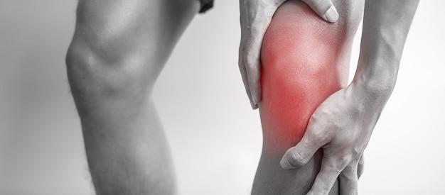 灰色の背景に筋肉痛のある男。高齢者は、ランナー膝または膝蓋大腿痛症候群、変形性関節症、関節炎、リウマチ、および膝蓋腱炎による膝の痛みがあります。医療の概念