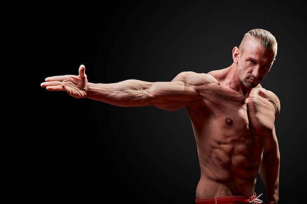 Man with muscled physique on black background.