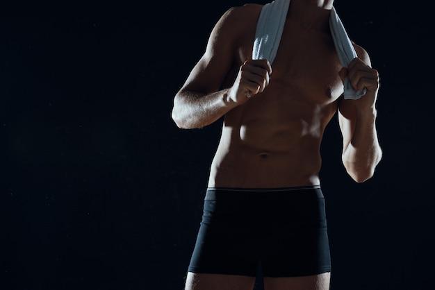 筋肉の腹筋を持つ男ジムの暗い背景のトリミングされたビュー