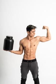 Мужчина с мускулистым телом держит черную бутылку одной рукой, показывая мускулистые бицепсы, стоит лицом вперед и смотрит в сторону