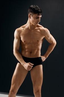 暗いパンティーでポーズをとる筋肉質の体を持つ男