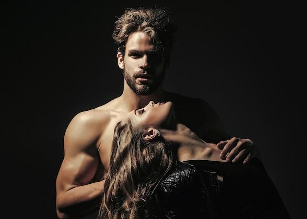 근육질의 몸통과 관능적 인 여자를 가진 남자. 검은 바탕에 사랑에 빠진 커플입니다. 뷰티, 패션 컨셉.