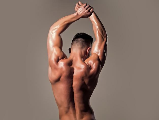 근육질의 젖은 몸과 등을 가진 남자. 강한 남자 또는 근육질 남자. 검은 배경에 포즈 근육 남자의 다시보기. 보디 빌더 및 스트립 테마. 벌거 벗은 몸통.