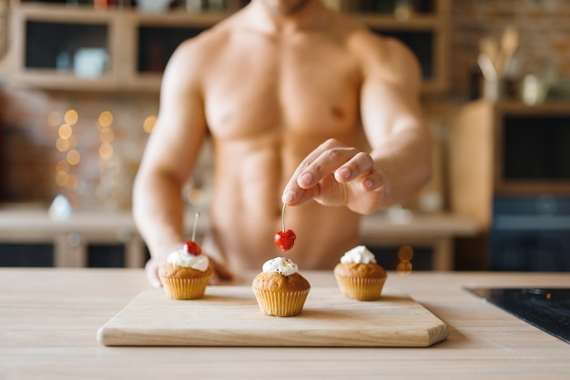 Man with naked body cooking cakes with cherry on the kitchen. nude male person preparing breakfast at home, food preparation without clothes