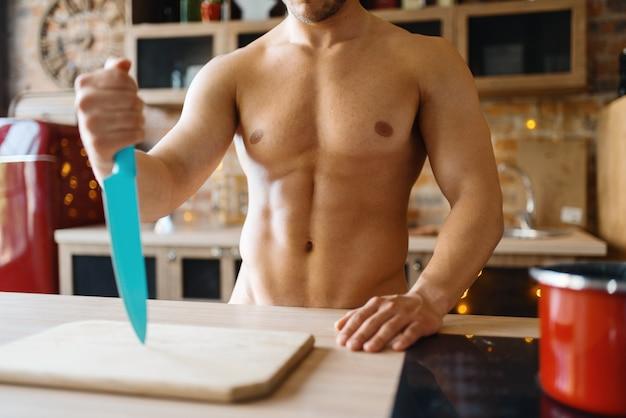 台所で料理する裸の体を持つ男。自宅で朝食を準備している裸の男性人、衣服なしの食事の準備