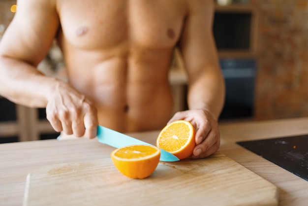 벌거 벗은 몸매를 가진 남자는 부엌에서 오렌지를 자릅니다. 집에서 아침 식사를 준비하는 누드 남성 사람, 옷없이 음식 준비