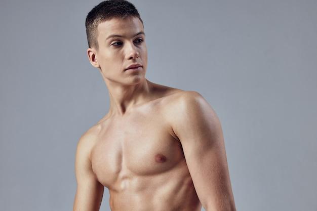 裸の体を持つ男は、胴体の魅力的な外観の孤立した背景をポンプアップ