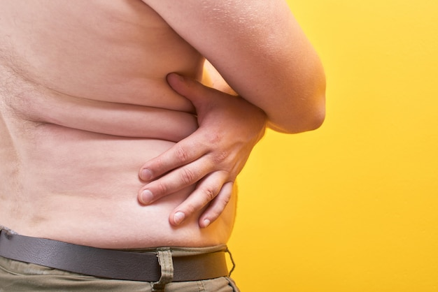 Man with naked body touches big fat belly on yellow background in studio closeup. concept of obesity, fast and junk food, sports, liposuction, weight loss, parameters