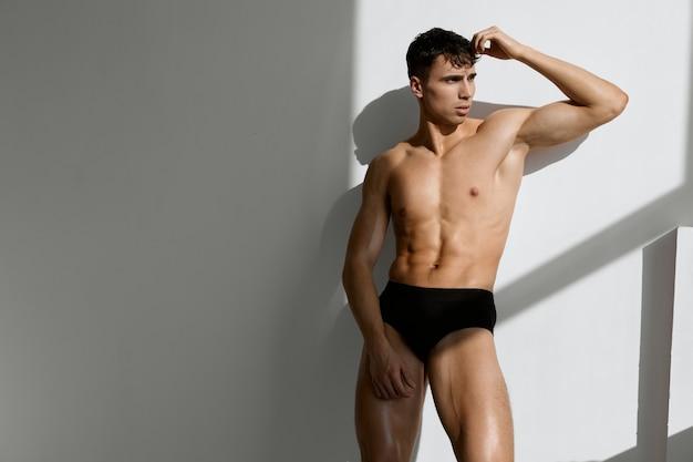 Мужчина с обнаженным мускулистым телом в черных трусиках позирует