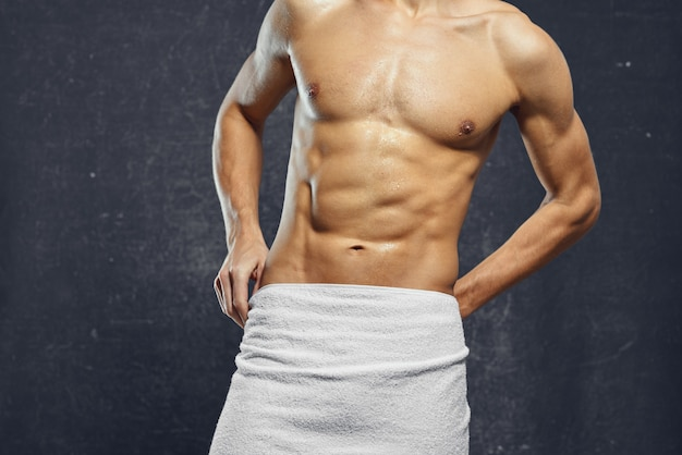 A man with a naked pumpedup torso covers himself with a towel fitness bodybuilders