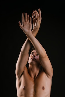 Man with naked torso crossing arms raising up