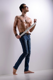 Man with a naked torso posing on a white.