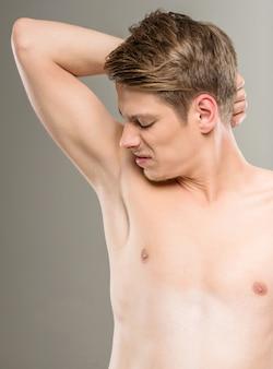 Man with naked torso smells his armpits