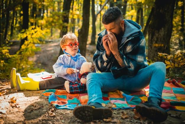 Мужчина с салфеткой чихает в желтом парке, папа и сын играют вместе, папа и сын в свитерах в ...