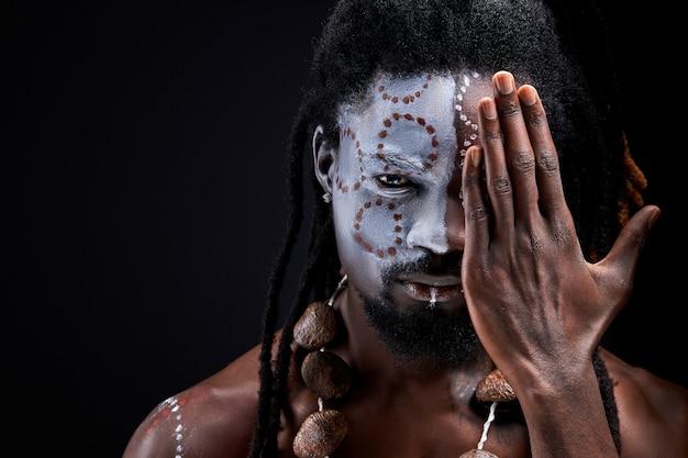 顔の半分を閉じる国民の化粧を持つ男