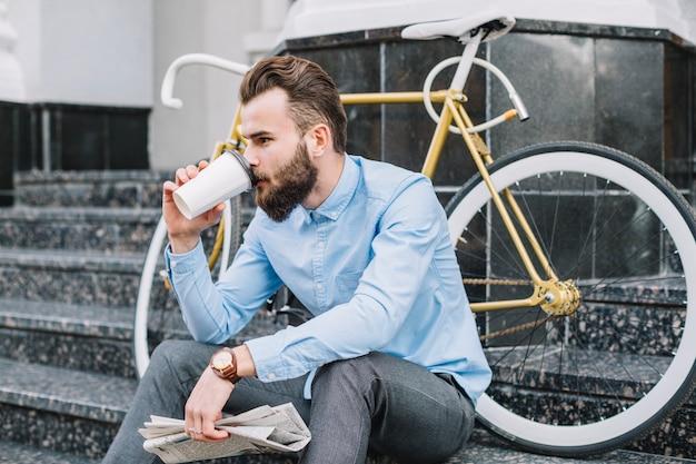 Человек с газетным напитком горячего напитка