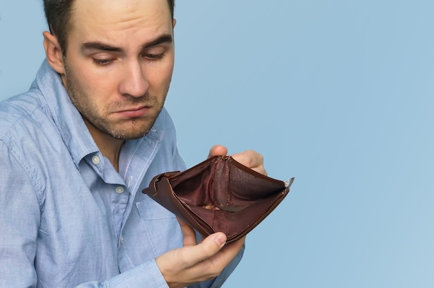 돈이 없는 남자. 빈 지갑을 들고 사업가입니다. 남자는 불일치와 돈 부족을 보여주고 대출과 모기지를 지불할 수 없어 빈 지갑을 보여줍니다.