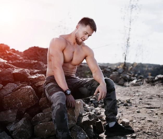 シャツを着ていない男が岩の上に座っています。運動選手またはボディービルダーの人。自然の風景。