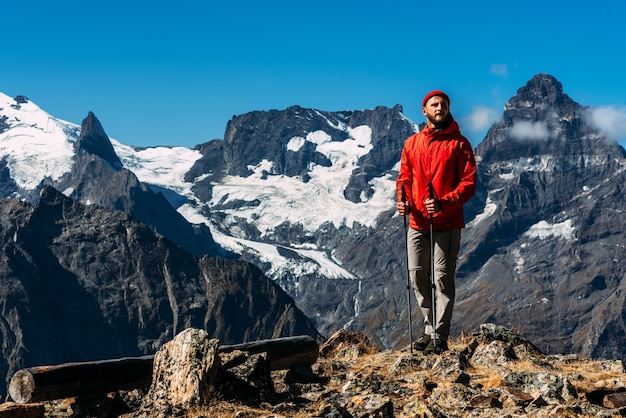 A man with nordic walking sticks in the mountains. a man traveling in the caucasus. mountain sports. mountain tourism. walking tour. the journey to the mountains. nordic walking among the mountains.