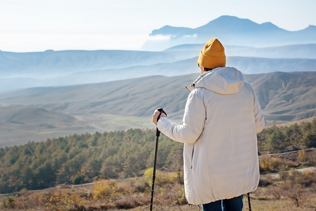 A man with nordic walking sticks stands high in the mountains. view from the back.