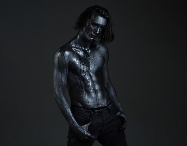 반짝이는 은색 페인트 아트로 덮인 누드 몸통을 가진 남자 섹시한 남자 몸