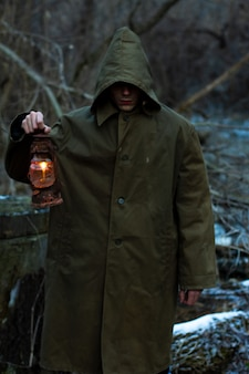 A man with an old glowing lantern in a raincoat in a dark forest . silhouette of a cult, a person conducts a ritual in a magical forest. the concept of occultism. soft focus