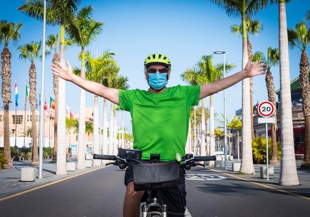 テネリフェ島の人けのない道で自転車に乗って両手を広げて医療用マスクを持った男