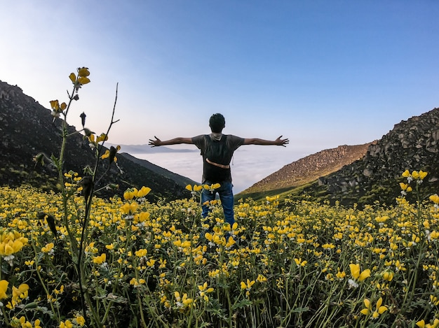 Man with open arms standing over flower landscape of a mountainous valley