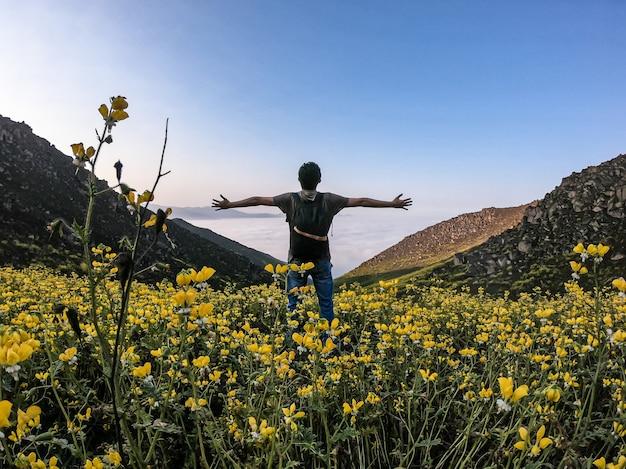 山の谷の花の風景の上に立っている両手を広げて男