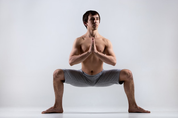 Man with open legs and folded hands