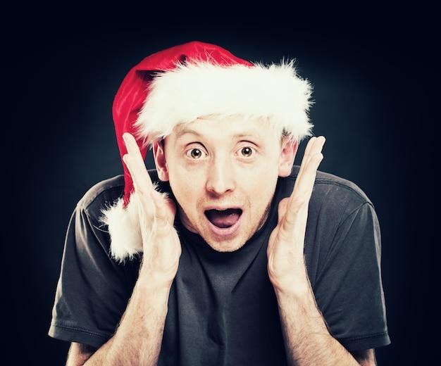 口を開けた男。暗闇の中でクリスマスサンタ帽子で驚いた男