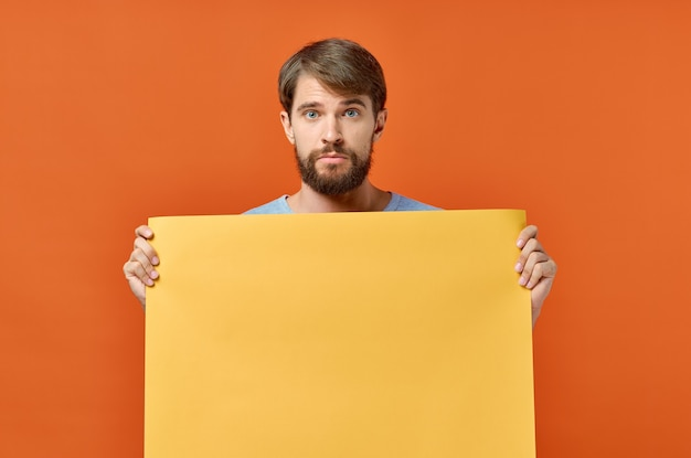 Man with orange sheet of paper poster mockup marketing isolated