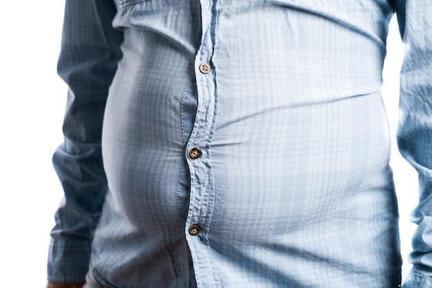 Man with overweight. symbolic photo for beer belly, unsuccessful dieting and eating the wrong foods. weight loss concept. tight shirt.
