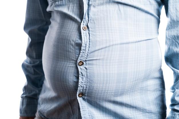 과체중을 가진 남자. 맥주 배, 실패한 다이어트 및 잘못된 음식 섭취에 대한 상징적 인 사진. 체중 감량 개념. 타이트한 셔츠.
