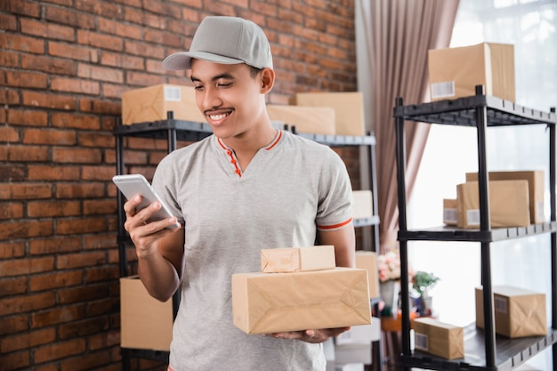 Человек с пакетом, держа смартфон