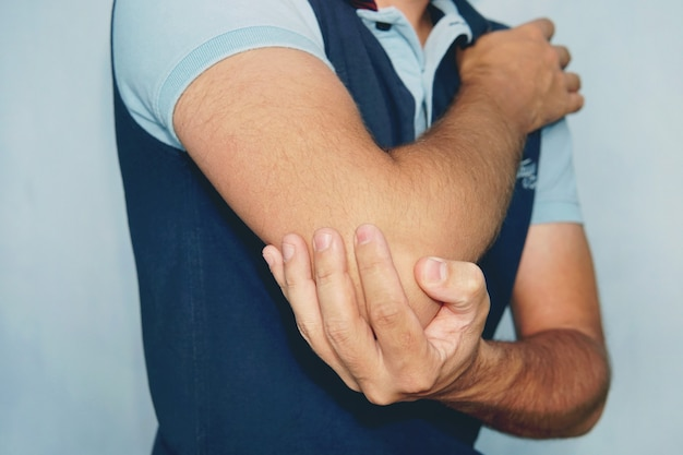 Man with pain in elbow. pain relief concept.